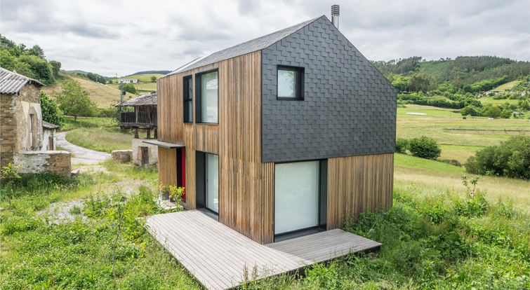 casa modular en Asturias con cubierta inclinada y una parte de la fachada revestidas de pizarra