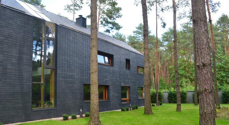 casa moderna diseñada con pizarra, madera y grandes ventanales