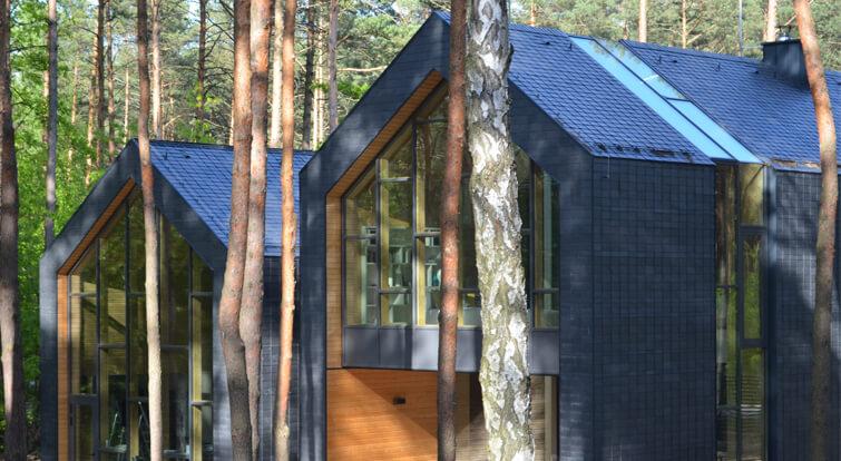 bonita casa recubierta de pizarra rodeada integrada en un espacio natural