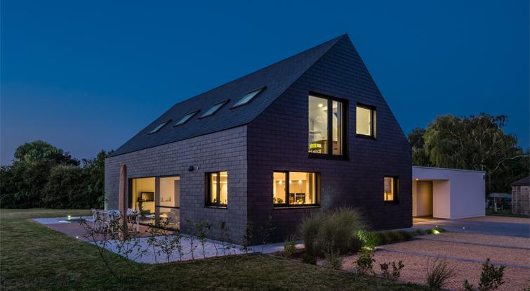 moderna casa con revestimiento de pizarra en cubierta y fachada